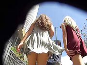 La candidata telecamera in pubblico sta filmando due ragazze sexy da dietro